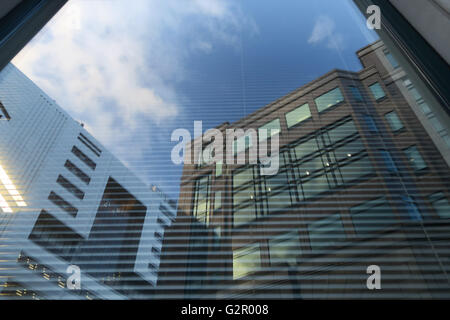 large commercial buildings/skyscrapers against sky reflected in glass - Stock Photo