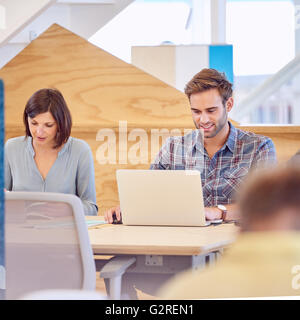 Male and female students busy studying hard together - Stock Photo