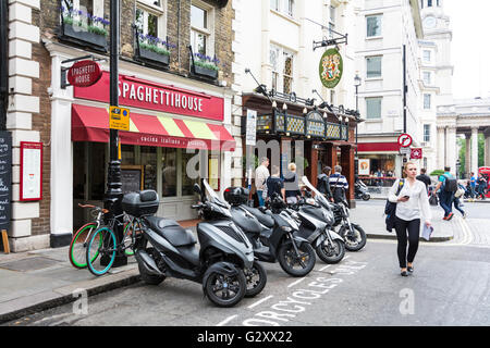 A young woman, with mobile phone in her hand, passes in front of Spaghetti House on St Martins Lane, London, WC2H, - Stock Photo