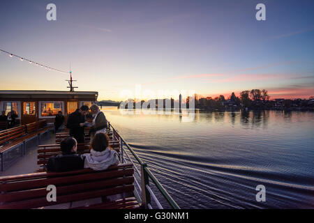 View from a passenger boat on the Chiemsee with the Fraueninsel and the Alps at sunset, Germany, Bayern, Bavaria, - Stock Photo