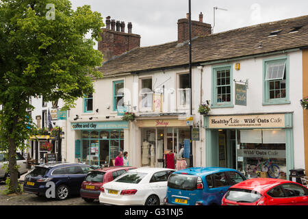 People pass independent shops, cafés and parked cars, on the High Street of the historic market town of Skipton, - Stock Photo