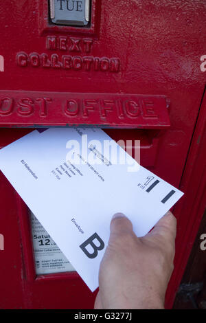 Exeter UK 7 June 2016 EU referendum voting by postal ballot posting vote into a post box. Last day to apply for - Stock Photo