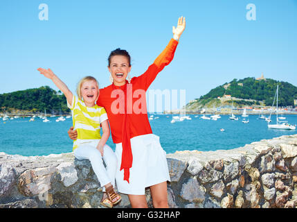 Luxury weekend with family. Portrait of happy mother and daughter rejoicing in front of the beautiful scenery overlooking - Stock Photo
