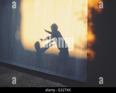 Shadows of two children playing against wall - Stock Photo