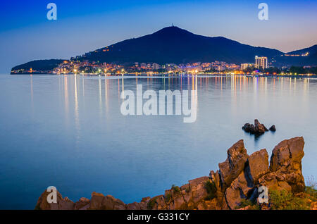 Coastline of illuminated Budva in Montenegro. Landscape of european town near the sea. - Stock Photo