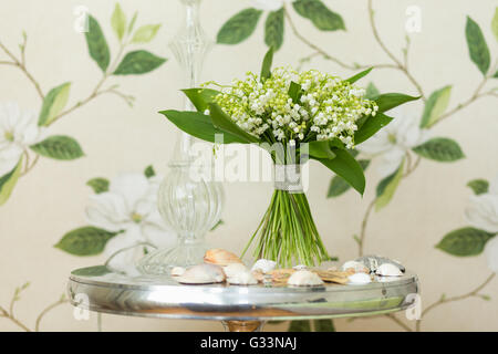 Small bouquet of Lily of the valley flowers standing on decorative metallic table with sea shells elements. Flower - Stock Photo