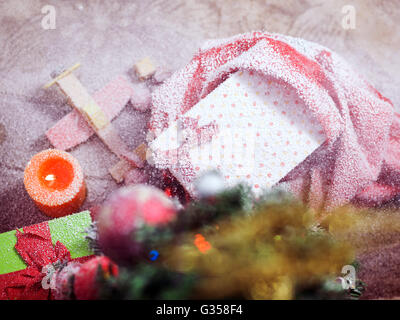 Christmas candles and fir tree branches on a wooden background with toys - Stock Photo