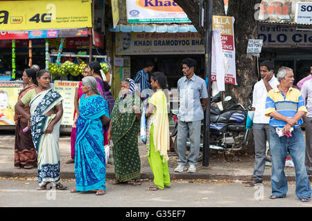A group of Indian people waiting for a local bus in Mylapore, Chennai, Tamil Nadu, India, Asia - Stock Photo