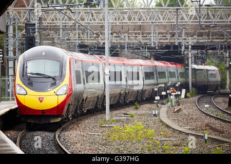 Stockport train station a Alstom Class 390 Pendolino  electric high-speed train operated by Virgin Trains leaves - Stock Photo