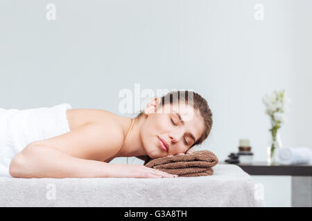 Tender young woman lying on towel with eyes closed during skin care treatment in spa salon - Stock Photo