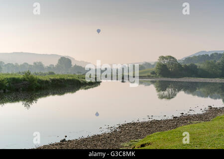 First light at Reeth in Swaledale, The Yorkshire Dales, and a hot air balloon over the River Swale. - Stock Photo