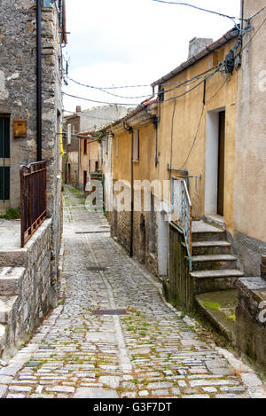 Old narrow cobbled street leading between residential houses in an Italian town on a gray sky day - Stock Photo