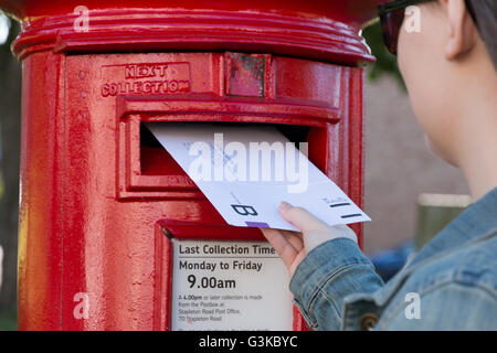 A young lady posting a postal ballot in the UK. - Stock Photo
