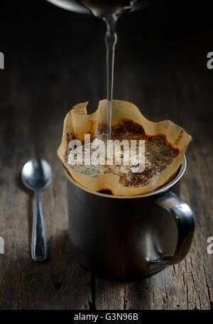 Ground coffee in metal cup and filter holder - Stock Photo