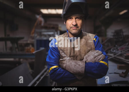 Portrait of welder standing with arms crossed in workshop - Stock Photo