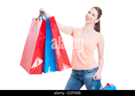 Beautiful young woman holding few shopping bags, smiling and feeling satisfied or content isolated on white background - Stock Photo