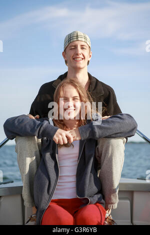 Sweden, Sodermanland, Stockholm Archipelago, Portrait of teenage girl (16-17) and young man sitting on boat - Stock Photo