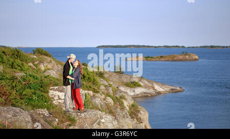 Sweden, Sodermanland, Stockholm Archipelago, Teenage girl (16-17) and young man embracing by sea - Stock Photo