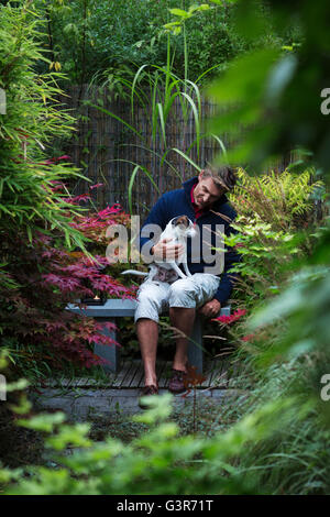 Sweden, Uppland, Man sitting with dog on bench in Japanese garden - Stock Photo