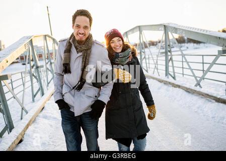 Sweden, Vasterbotten, Umea, Young couple walking on footbridge in winter - Stock Photo