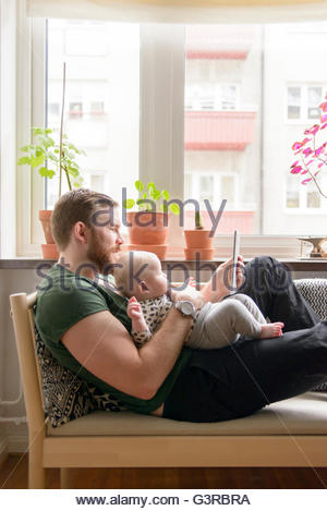 Sweden, Father holding baby boy (0-1 months) and using digital tablet - Stock Photo