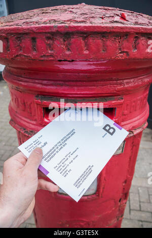 London, UK. 15th June, 2016. Posting a vote for the EU referendum in a traditional red letter box. Credit:  Guy - Stock Photo