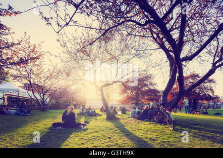 Sweden, Skane, Malmo, People sitting on grass in park - Stock Photo