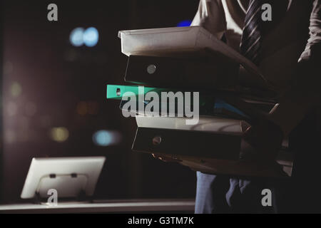 Businessman carrying folder at night - Stock Photo