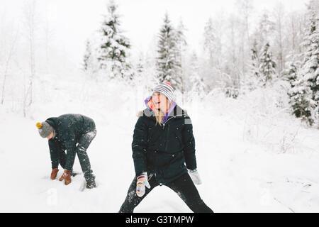 Finland, Jyvaskyla, Saakoski, Young couple having snowball fight - Stock Photo