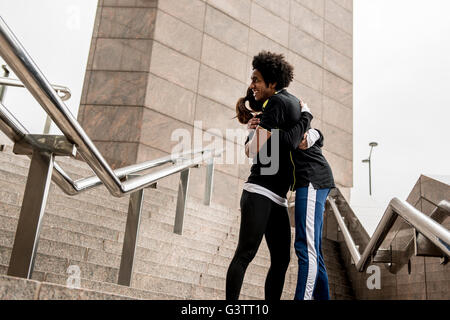A young couple embracing before a jog along the South Bank in London. - Stock Photo
