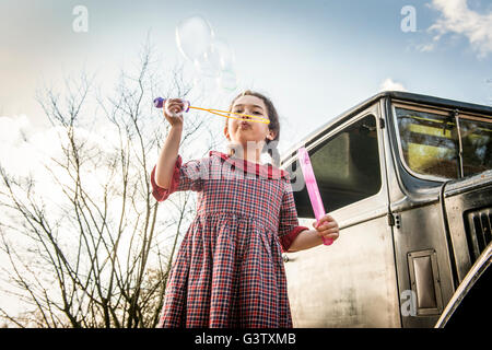 A young girl blowing bubbles in front of a vintage car. - Stock Photo