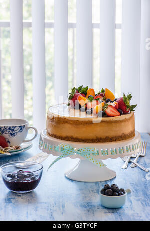 Caramel cheesecake with lemon curd on cakestand with blueberry sauce, decorated with fresh berries. Selective focus, - Stock Photo