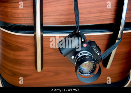 Leica SL digital camera hanging on an Eames Chair. - Stock Photo