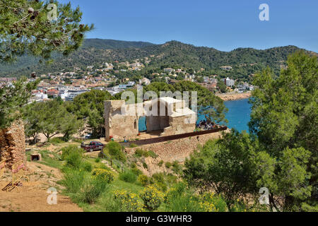 View of ruins of church in medieval fortress of Tossa and tourists on excursion on on May 24, 2016 in Tossa de Mar, - Stock Photo