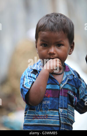 A portrait of a poor little Indian boy putting finger in his mouth. - Stock Photo
