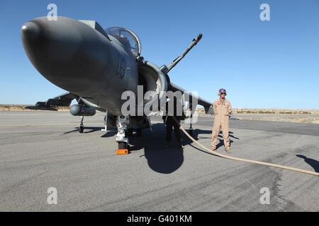 U.S. Marine Corps air crewmen refuel an AV-8B Harrier II aircraft. - Stock Photo