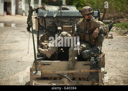 A coalition forces member maintains security from an all-terrain vehicle. - Stock Photo