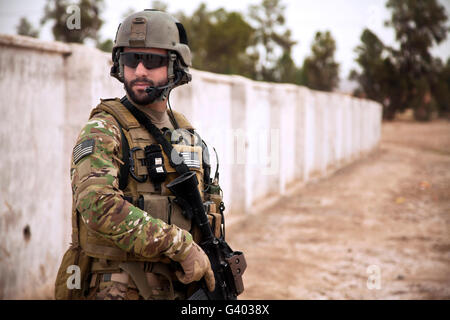 A coalition force member maintains security during a patrol. - Stock Photo