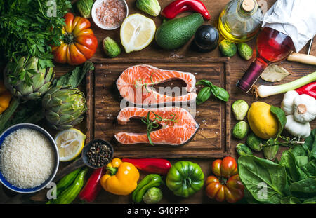 Raw uncooked salmon steak with vegetables, rice, herbs, spices and wine bottle on chopping board over rustic wooden - Stock Photo