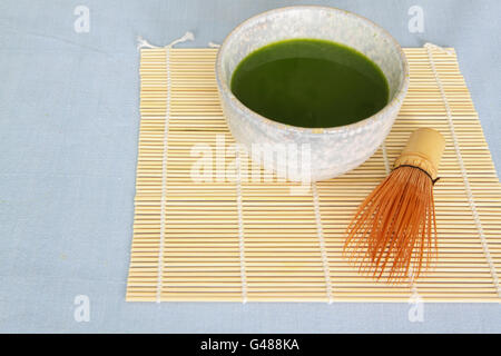 Matcha green tea in stone drinking bowl on Bamboo placemat with wooden whisk in front of bowl on light blue tablecloth. - Stock Photo