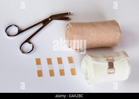 Bandage scissors, plasters and bandages - Stock Photo