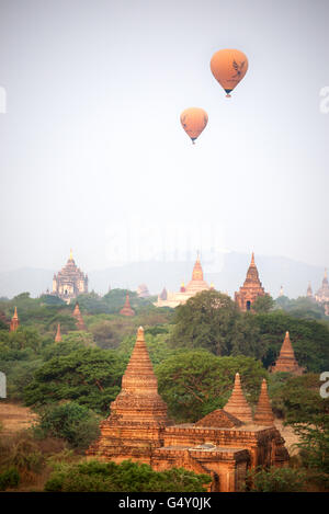 Hot-air balloons flying over Bagan temples at dawn, Old Bagan Archaelogical Zone, Mandalay Region, Myanmar - Stock Photo