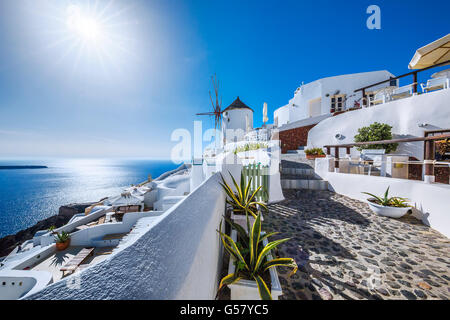 Oia village with sun, Santorini island, Greece - Stock Photo