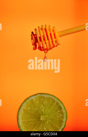 Honey flowing on lemon over yellow background - Stock Photo