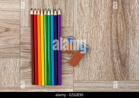 Lots of assorted colors pencils and erasers on wooden background, rainbow - Stock Photo