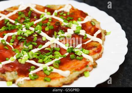 okonomiyaki Osaka style with mayonnaise, onion and sauce - Stock Photo
