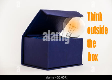 Blue box on white background with Think outside the box text - Stock Photo
