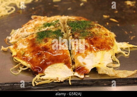 Mouth-watering Okonomiyaki, served Hiroshima-style in Hiroshima, Japan - Stock Photo