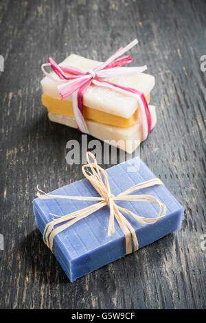 Colorful handmade soaps tied with strings on rustic wooden background - Stock Photo