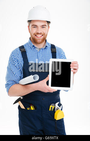Smiling handsome young builder holding blank screen tablet - Stock Photo